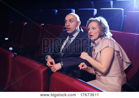 Young adult couple in cinema movie theater scared while watching horror film.