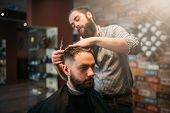 Coiffeur cutting by scissors hair of customer man poster