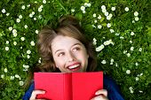 Woman lying on grass with book