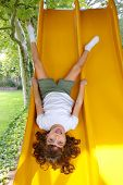 Brunette little girl upside down playground slide forest tree park