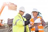 Engineers discussing over documents at construction site poster