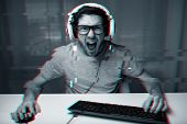 technology, gaming, entertainment and people concept - angry screaming young man in headset with pc  poster