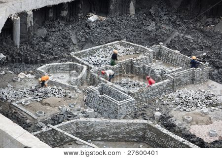 Building site,Masons building brick wall  of  a concrete pipe caps in a basement of a multi-storey building.The frame of  brick wall are used  for  pipe caps to provide a suitable stable foundation.