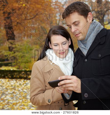 Happy couple in fall using mobile internet with smartphone