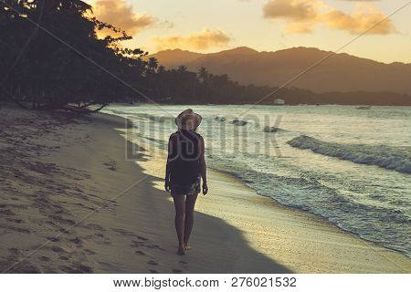 poster of Traveler Girl Walking On Tropical Beach In Sunset. Vintage Photo Of Young Girl Traveler In Vacation.