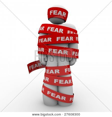A man is wrapped in red tape reading fear representing the paralysis of being afraid and unable to move or act in the face of danger or something that scares or induces fright