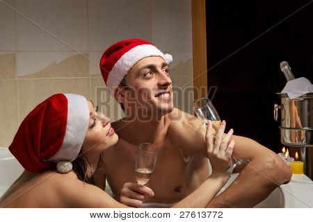 A young beautiful couple in santa hats is enjoying a bath with champagne in a glasses