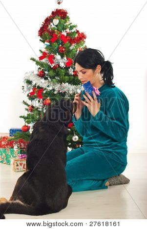 Woman Sharing Christmas Gift With Her Dog
