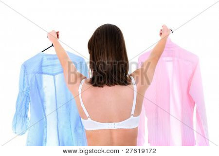 A portrait of a young woman trying to decide between two shirts over white background