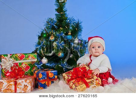 Charming baby (girl) in Santa Claus suit, sitting beside a Christmas tree decorated and gifts. She h