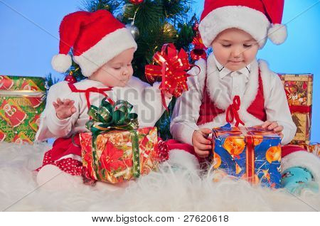 Two cute babies (girl and boy) dressed as Santa Claus. Children are near gifts and Christmas tree.