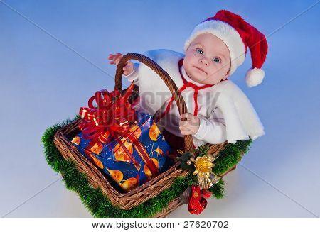 Santa Baby. niedliche kleine Mädchen gekleidet als Santa Claus sitzen in einem Korb mit einem Geschenk. Korb d