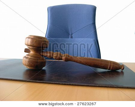 Old wooden gavel, a blue chair and a court desk