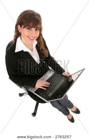 Businesswoman Sitting In Office Chair With Laptop