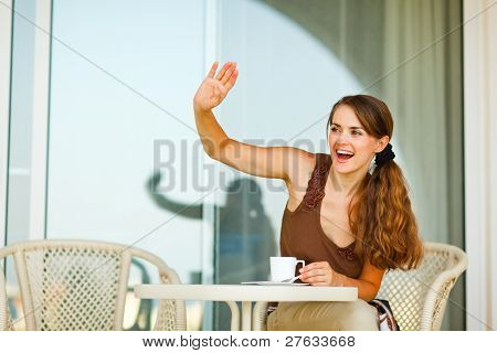 Smiling Beautiful Woman Sitting On Terrace With Cup Of Tea Greeting Someone