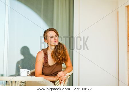 Thoughtful Young Female  Sitting On Terrace With Cup Of Tea And Looking In Corner