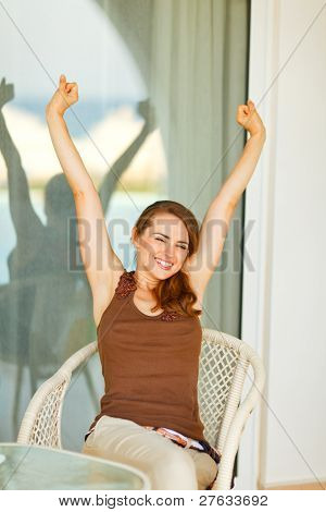 Beautiful Woman Sitting On Terrace And Stretching After Relaxing