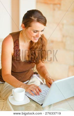 Jovem sorridente com café trabalhando no Laptop no terraço