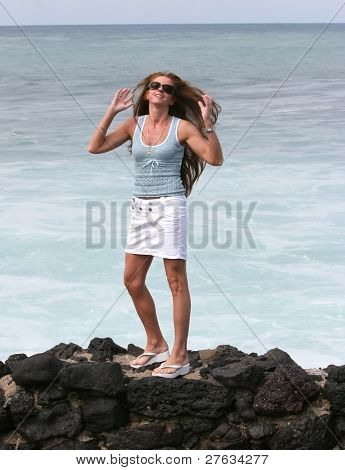 Smiling woman standing on the rocks