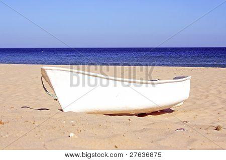 einem einsamen weißen Boot am Strand