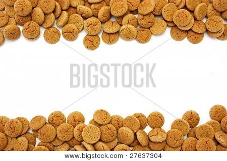 Gingerbread nuts, a typical dutch delicacy scattered around on the 5th of december, the day of santa claus in Holland,  with copyspace isolated on white