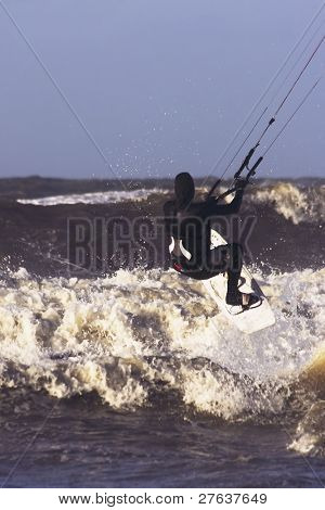 Kite surfer jumping on the waves at the north sea in the Netherlands