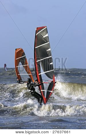 Windsurfers surfing the waves in the Netherlands