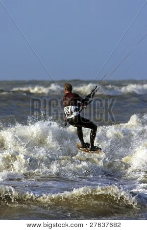 Kite surfer surfing the waves on the north sea in the Netherlands
