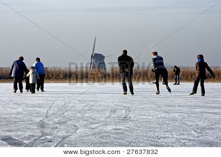 Traditional dutch winter image, ice skating in the fields from Holland