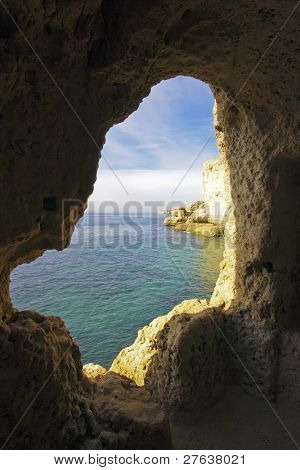 View through a hole in a rock at the atlantic ocean in the Algarve in Portugal