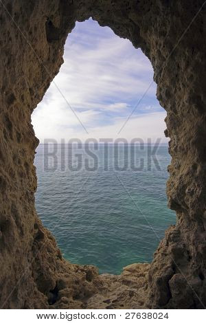 View through a hole in a rock at the atlantic ocean in Portugal