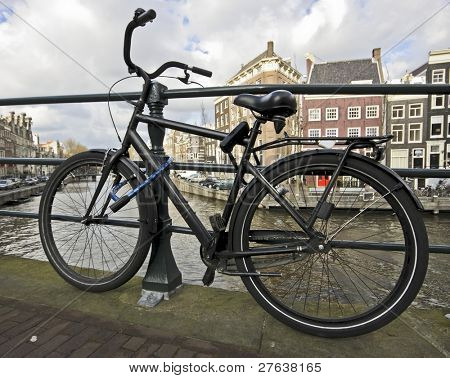 Black bike chained at the bridge from an Amsterdam canal in the Netherlands