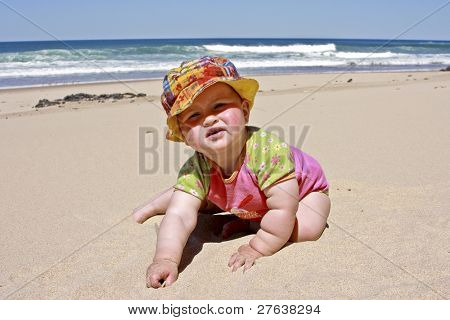 Cute little baby girl  crawling in the sand at the beach