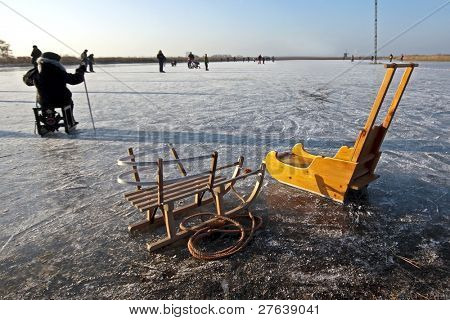 Sledges in wintertime on a frozen lake in the Netherlands