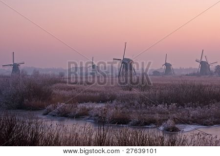 Ancient windmills at Kinderdijk at sunset in winter in the Netherlands