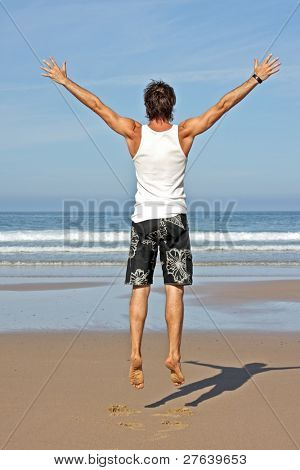 Young man jumping in the air out of joy at the atlantic ocean