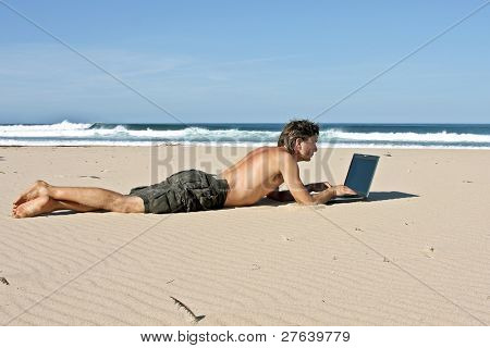 Young guy working on his laptop on the beach