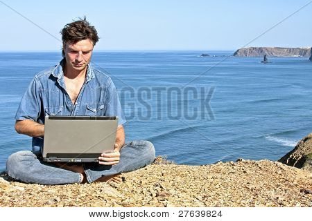 Young guy working on his laptop on a rock at the ocean