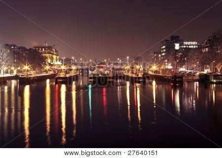 Ver compuertas en el río Amstel en citycenter de Amsterdam en los países bajos en la noche