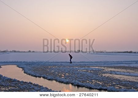 Lonely iceskater at sunset in the countryside from the Netherlands in winter