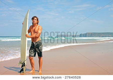 Surfer and his surfboard at the beach ready to surf on the atlantic ocean