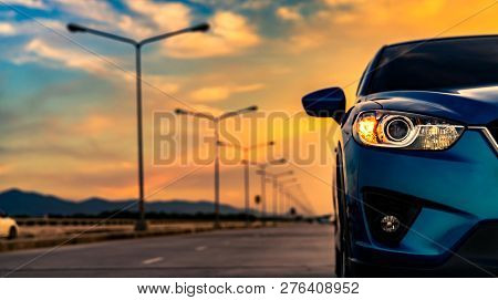 poster of Blue Compact Suv Car Open Headlamp Light Parked On Concrete Road Near The Mountain At Sunset With Be