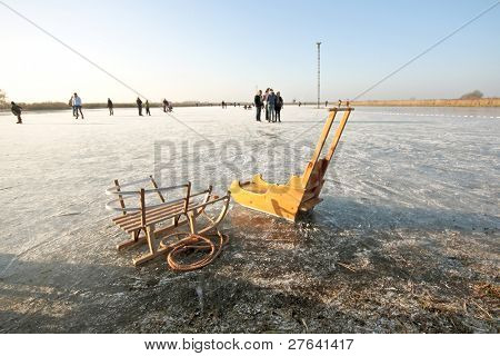 Old fashioned sledges on a frozen lake in the countryside from the Netherlands