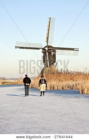 Typically dutch: ice skating on a frozen canal  with view on a windmill on a cold winterday in the Netherlands
