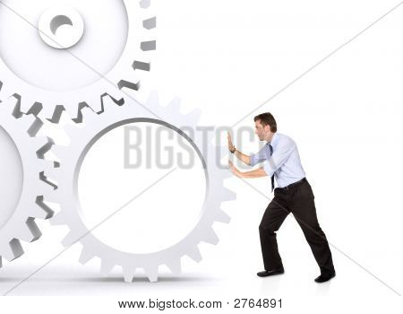 Business Man Pushing A Cogwheel