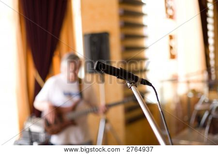Microphone On Tripod With Guitarist At Background