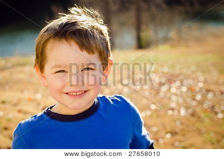 Portrait of happy young boy outdoors in image with copy space