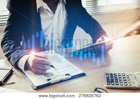 poster of Investor Or Business Man Analysis On Financial Reports And Using Mobile Tablet With Graphic Candle S