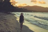 Traveler Girl Walking On Tropical Beach In Sunset. Vintage Photo Of Young Girl Traveler In Vacation. poster