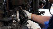 Mechanic In Working Gloves Choosing Tool While Repairing Car In Auto Service. Scene. Selective Focus poster